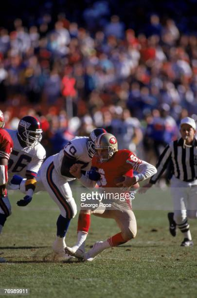 Joe Montana the San Francisco 49ers gets sacked by New York Giants defensive tackle Leonard Marshall during the 1990 NFC Championship game at...