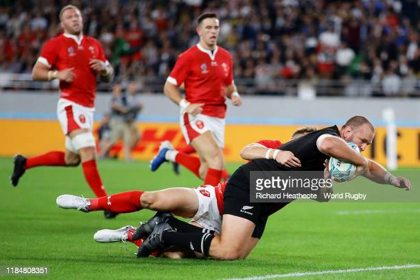 Joe Moody of New Zealand goes over to score his team's first try under pressure from Hallam Amos of Wales during the Rugby World Cup 2019 Bronze...