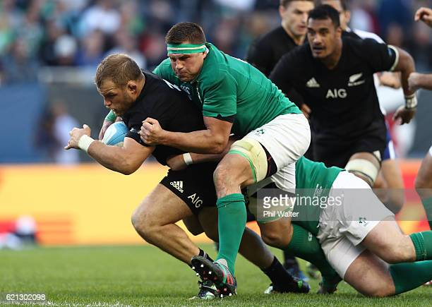 Joe Moody of New Zealand is hauled down by CJ Stander of Ireland during the international match between Ireland and New Zealand at Soldier Field on...