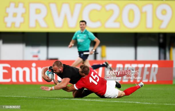 Joe Moody of New Zealand touches down to score his team's first try under pressure from Hallam Amos of Wales during the Rugby World Cup 2019 Bronze...