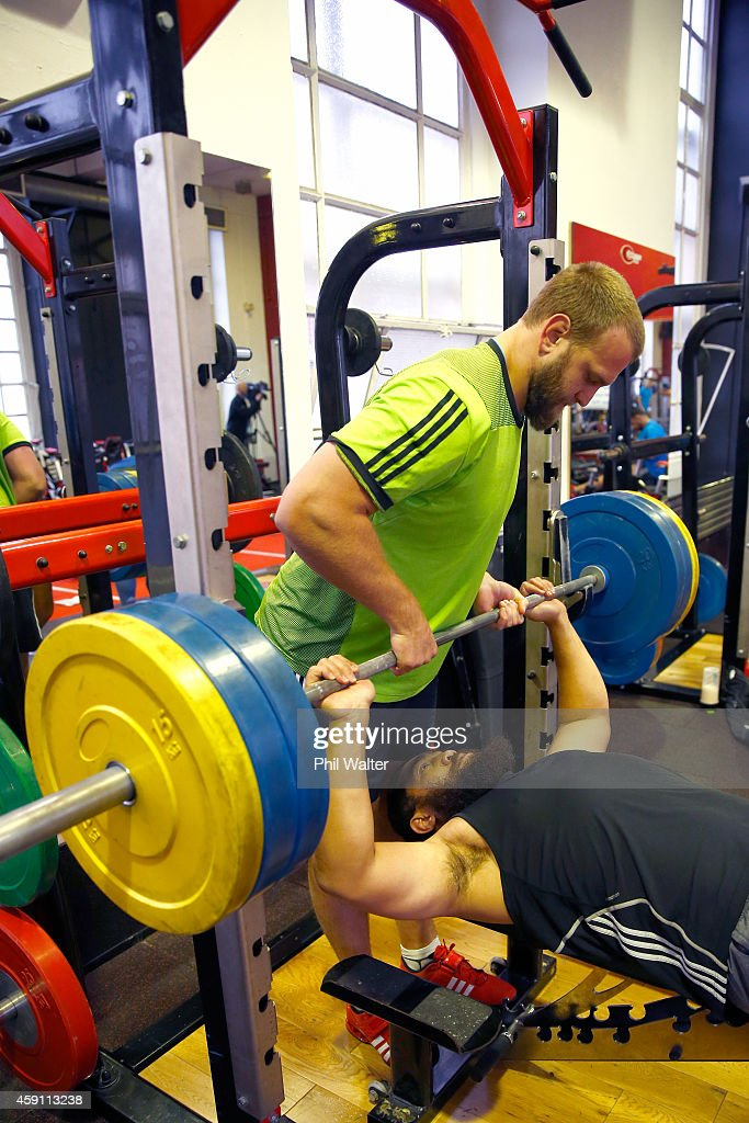 Joe Moody of the All Blacks assists Charlie Faumuina during a New Zealand All Blacks Gym session at the Cardiff University Strength and Conditioning Centre on November 17, 2014 in Cardiff, Wales.