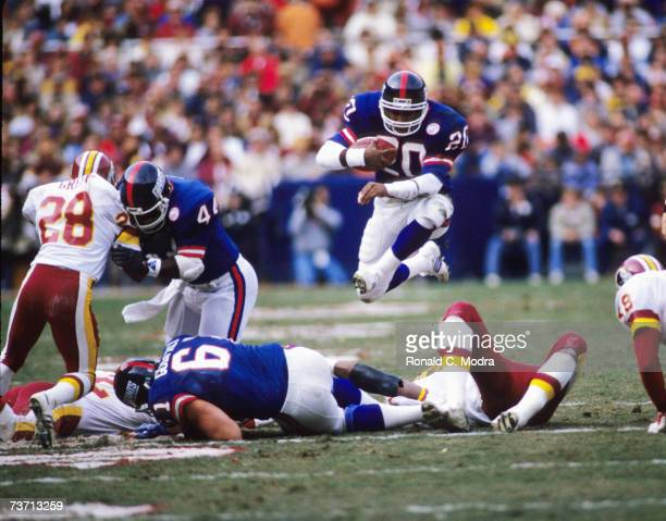 Joe Morris of the New York Giants jumping over players during a game against the Washington Redskins in December 7 1986 in Washington District of...