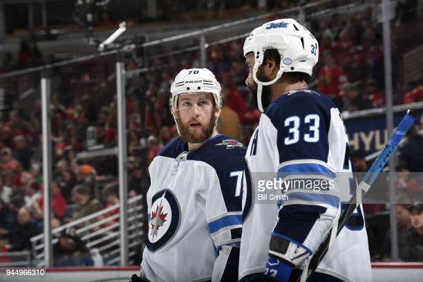 Joe Morrow and Dustin Byfuglien of the Winnipeg Jets talk in the third period against the Chicago Blackhawks at the United Center on March 29 2018 in...