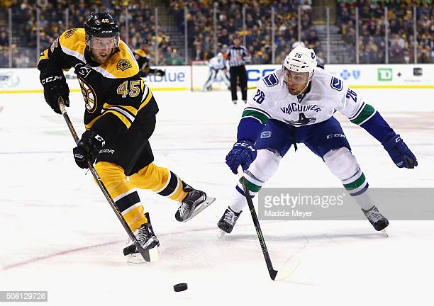 Joe Morrow of the Boston Bruins and Emerson Etem of the Vancouver Canucks battle for control of the puck during the second period at TD Garden on...