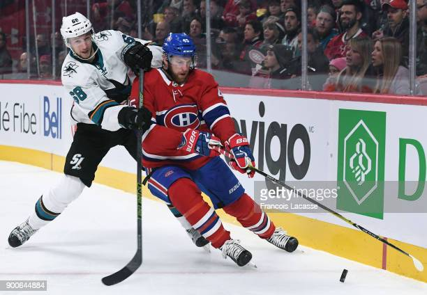 Joe Morrow of the Montreal Canadiens controls the puck against Melker Karlsson of the San Jose Sharks in the NHL game at the Bell Centre on January 2...