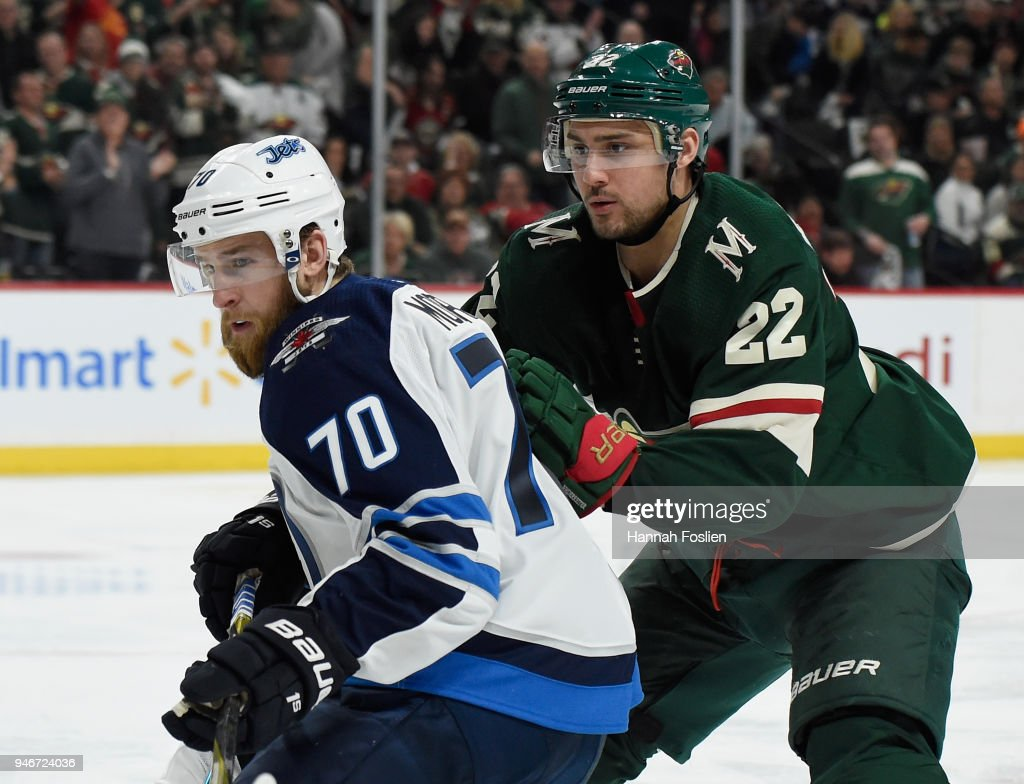 Joe Morrow #70 of the Winnipeg Jets and Nino Niederreiter #22 of the Minnesota Wild skate after the puck during the second period in Game Three of the Western Conference First Round during the 2018 NHL Stanley Cup Playoffs at Xcel Energy Center on April 15, 2018 in St Paul, Minnesota. The Wild defeated the Jets 6-2.