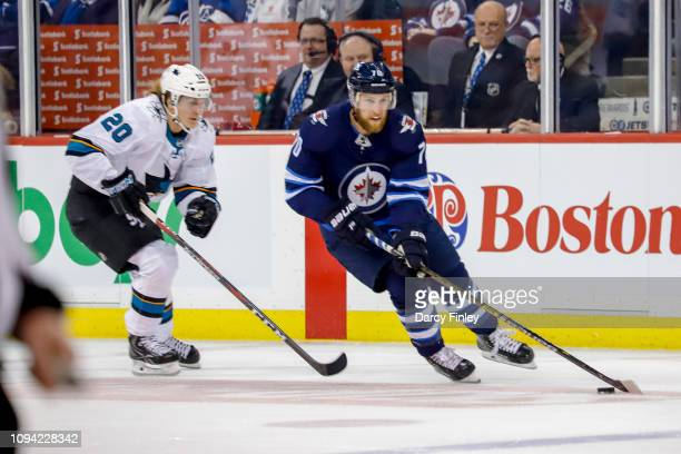 Joe Morrow of the Winnipeg Jets plays the puck down the ice as Marcus Sorensen of the San Jose Sharks gives chase during first period action at the...
