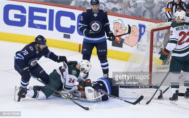 Joe Morrow of the Winnipeg Jets pulls Matt Dumba of the Minnesota Wild off Jets goalie Connor Hellebuyck in Game One of the Western Conference First...