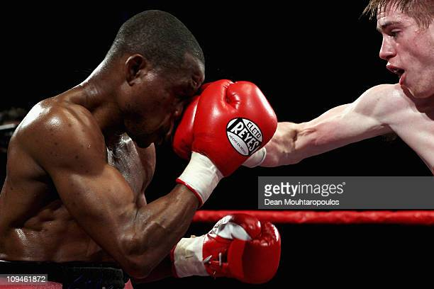 Joe Murray of England lands a blow on Daniel Kodjo Sassou of France in their featherweight fight during the Night of Champions Boxing at Reebok...