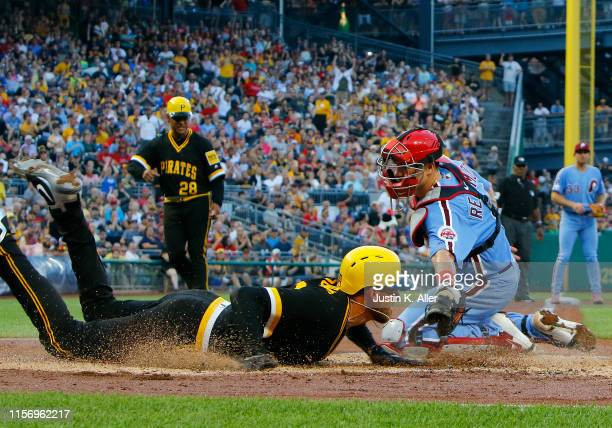 Joe Musgrove of the Pittsburgh Pirates scores on a RBI single in the third inning against J.T. Realmuto of the Philadelphia Phillies at PNC Park on...