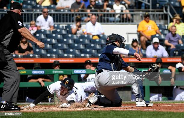 Joe Musgrove of the Pittsburgh Pirates slides safely past Omar Narvaez of the Seattle Mariners to score a run on a RBI single by Kevin Newman in the...