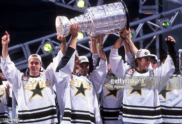 Joe Nieuwendyk Derian Hatcher Sergei Zubov and Mike Modano of the Dallas Stars hold the Stanley Cup Trophy during the 1999 Stanley Cup Parade after...