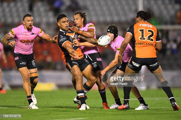 Joe Ofahengaue of the Tigers offloads the ball during the round 24 NRL match between the Penrith Panthers and the Wests Tigers at Moreton Daily...