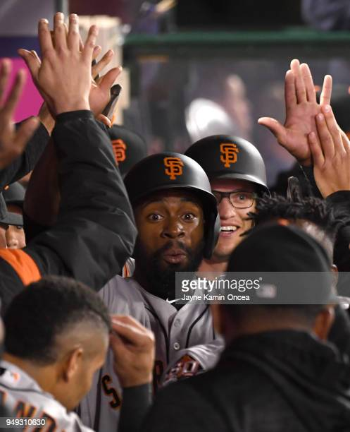 Joe Panik and Kelby Tomlinson of the San Francisco Giants are greeted in the dugout after scoring on the three run home run by Andrew McCutchen of...