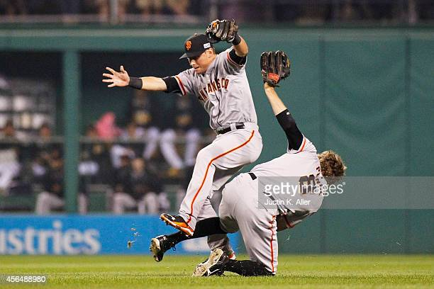 Joe Panik catches a ball hit by Gaby Sanchez of the Pittsburgh Pirates as he collides with Hunter Pence of the San Francisco Giants to end the second...