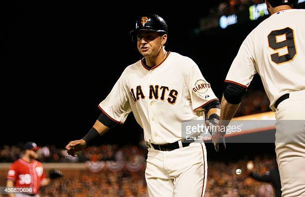 Joe Panik celebrates with Brandon Belt of the San Francisco Giants as he scores on a wild pitch in the seventh inning against the Washington...