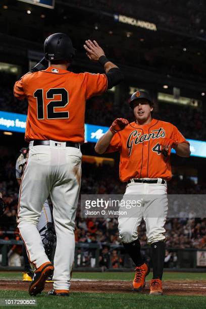 Joe Panik of the San Francisco Giants and Derek Holland celebrate after both scored runs on a single by Buster Posey during the third inning against...