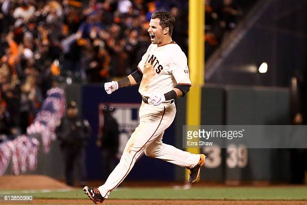 Joe Panik of the San Francisco Giants celebrates after doubling in the game winning run in the thirteenth inning against the Chicago Cubs during Game...