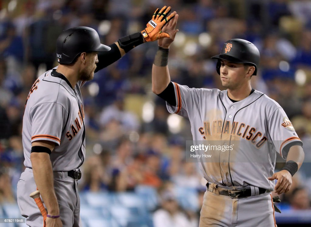Joe Panik #12 of the San Francisco Giants celebrates his run with Hunter Pence #8 to take a 2-1 lead over the Los Angeles Dodgers during the 11th inning at Dodger Stadium on May 3, 2017 in Los Angeles, California.