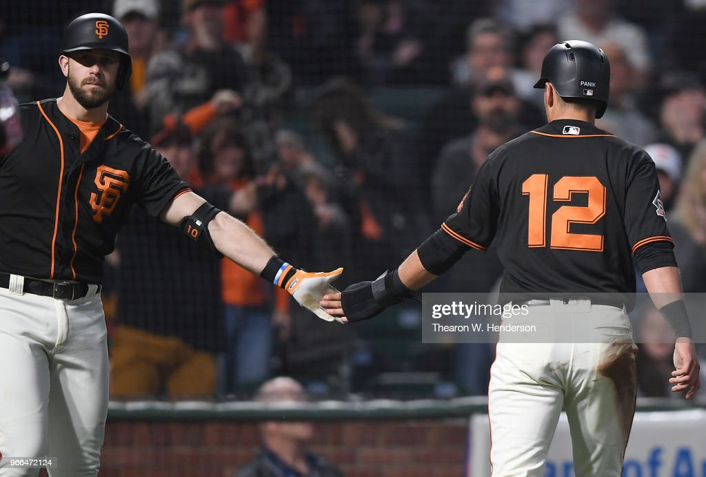 Joe Panik #12 of the San Francisco Giants is congratulated by Evan Longoria #10 after Panik scored against the Philadelphia Phillies in the bottom of the six inning at AT&T Park on June 2, 2018 in San Francisco, California.