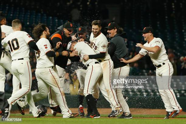 Joe Panik of the San Francisco Giants is mobbed by teammates after hitting a walkoff tworun single in the bottom of the ninth inning against the...