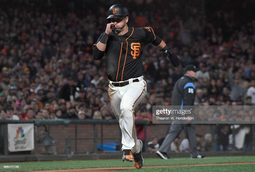 Joe Panik #12 of the San Francisco Giants races home from third base to score against the Philadelphia Phillies in the bottom of the eighth inning at AT&T Park on June 2, 2018 in San Francisco, California. Panik scored on a sacrifice fly from Andrew McCutchen #22.