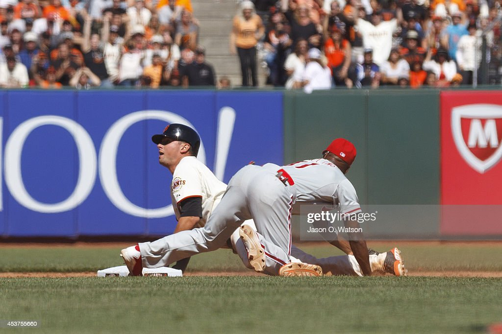 Joe Panik #12 of the San Francisco Giants safely slides into second base ahead of a tag from Jimmy Rollins #11 of the Philadelphia Phillies during the eighth inning at AT&T Park on August 17, 2014 in San Francisco, California.