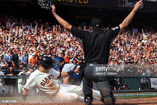 Joe Panik of the San Francisco Giants scores a run past Austin Barnes of the Los Angeles Dodgers during the sixth inning in front of umpire John...