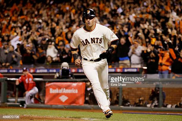 Joe Panik of the San Francisco Giants scores on a wild pitch in the seventh inning against the Washington Nationals during Game Four of the National...