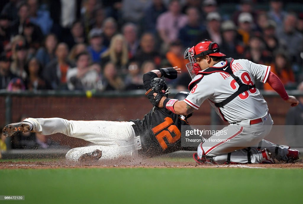 Joe Panik #12 of the San Francisco Giants scores sliding under the tag of Jorge Alfaro #38 of the Philadelphia Phillies in the bottom of the six inning at AT&T Park on June 2, 2018 in San Francisco, California.