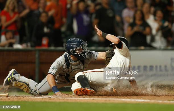 Joe Panik of the San Francisco Giants slides in safe at home plate against Austin Hedges of the San Diego Padres to score on a double hit by teammate...