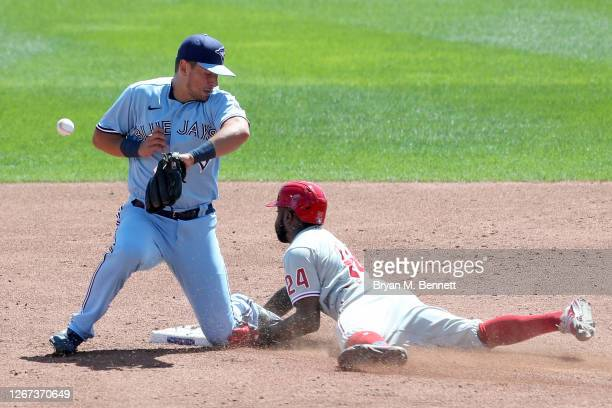 Joe Panik of the Toronto Blue Jays attempts to scoop a ball thrown by catcher Reese McGuire as Roman Quinn of the Philadelphia Phillies steals second...