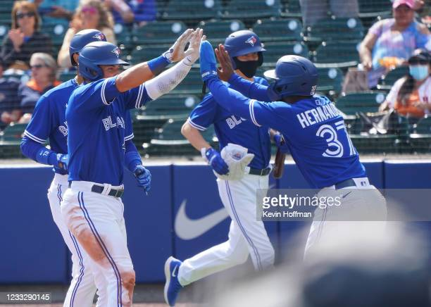 Joe Panik of the Toronto Blue Jays celebrates with Teoscar Hernandez after hitting a three run home run during the fourth inning against the Houston...