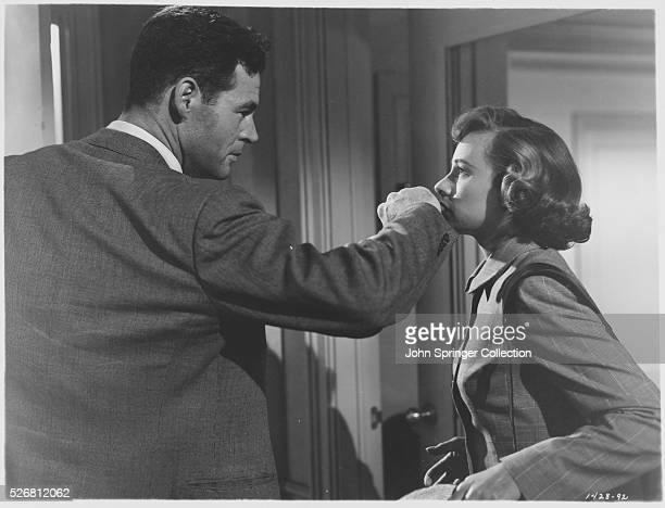 Joe Parkson prepares to cover Ann Sturges' mouth with his hand