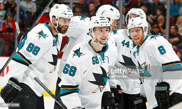 Joe Pavelski and Brent Burns congratulate Melker Karlsson of the San Jose Sharks who scored against the Vancouver Canucks during their NHL game at...