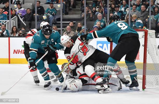 Joe Pavelski and Evander Kane of the San Jose Sharks fight to put the puck in the net against the New Jersey Devils at SAP Center on December 10 2018...