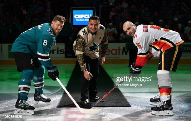 Joe Pavelski of the San Jose Sharks, 10-year army vet Javier Castillo and Mark Giordano of the Calgary Flames at center ice for the ceremonial puck...