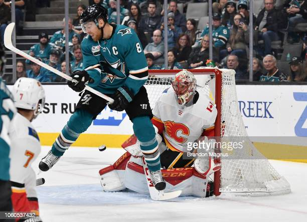 Joe Pavelski of the San Jose Sharks and Mike Smith of the Calgary Flames battle in front of the goal at SAP Center on November 11 2018 in San Jose...