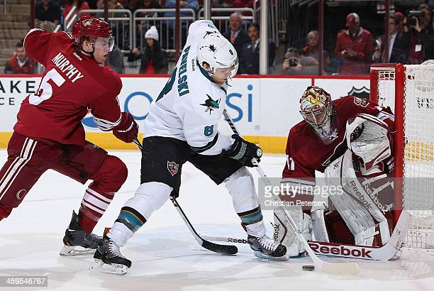 Joe Pavelski of the San Jose Sharks attemtps a shot on goaltender Mike Smith of the Phoenix Coyotes as Connor Murphy defends during the first period...