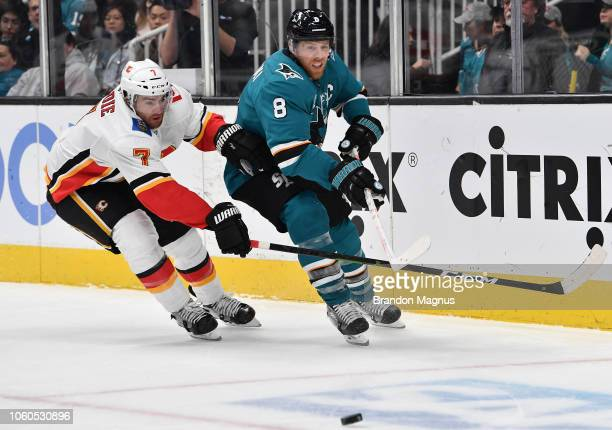 Joe Pavelski of the San Jose Sharks battles for the puck with TJ Brodie of the Calgary Flames at SAP Center on November 11, 2018 in San Jose,...