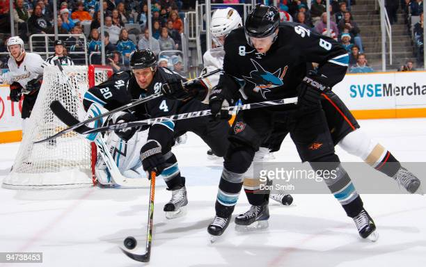 Joe Pavelski of the San Jose Sharks battles his opponent while linemate Rob Blake reaches in to snatch the puck during an NHL game against the...