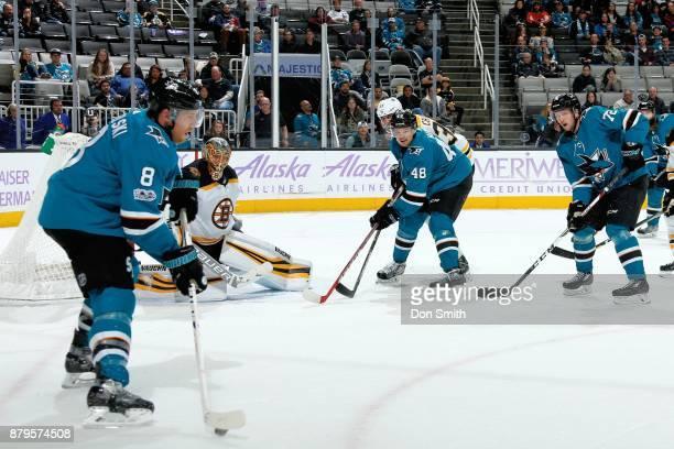 Joe Pavelski of the San Jose Sharks controls the puck as Anton Khudobin of the Boston Bruins along with Tomas Hertl and Tim Heed of the San Jose...