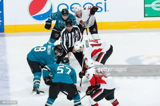Joe Pavelski of the San Jose Sharks faces off against Colin Greening of the Ottawa Senators during an NHL game on October 12, 2013 at SAP Center in...