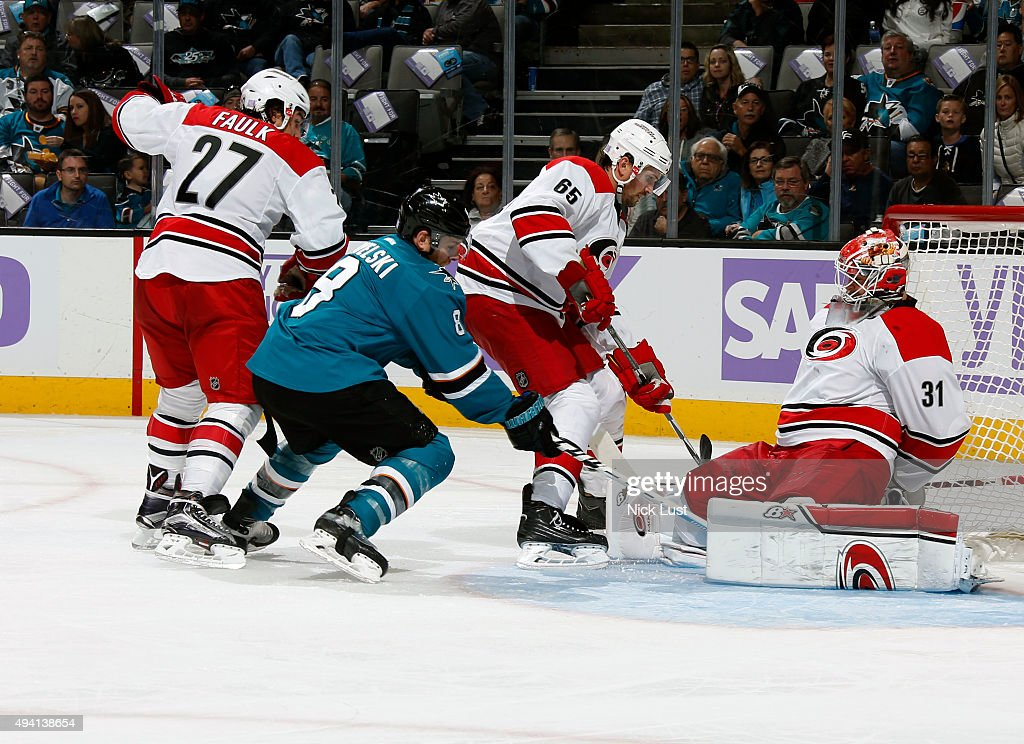 Joe Pavelski #8 of the San Jose Sharks gets his stick on the puck against Justin Faulk #27, Ron Hainsey #65, and Eddie Lack #31 of the Carolina Hurricanes during a NHL game at the SAP Center at San Jose on October 24, 2015 in San Jose, California.