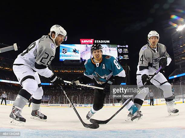 Joe Pavelski of the San Jose Sharks goes up against Jarret Stoll and Justin Williams of the Los Angeles Kings during the 2015 Coors Light NHL Stadium...
