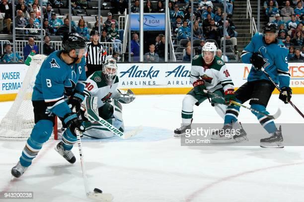 Joe Pavelski of the San Jose Sharks handles the puck as Devan Dubnyk and Nick Seeler of the Minnesota Wild and Evander Kane of the San Jose Sharks...