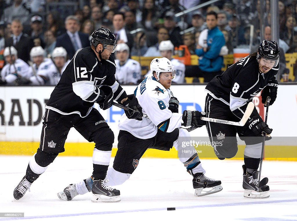Joe Pavelski #8 of the San Jose Sharks is checked by Marian Gaborik #12 and Drew Doughty #8 of the Los Angeles Kings during the first period in Game Four of the First Round of the 2014 NHL Stanley Cup Playoffs at Staples Center on April 24, 2014 in Los Angeles, California.