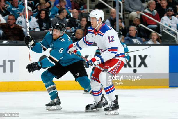 Joe Pavelski of the San Jose Sharks is defended by Peter Holland of the New York Rangers at SAP Center on January 25 2018 in San Jose California