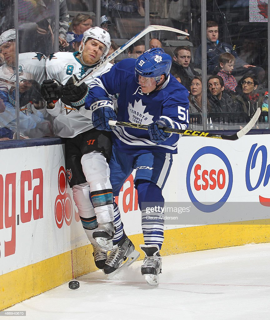 Joe Pavelski #8 of the San Jose Sharks is hammered into the boards by Jake Gardiner #51 of the Toronto Maple Leafs during an NHL game at the Air Canada Centre on March 19, 2015 in Toronto, Ontario, Canada. The Sharks defeated the Leafs 4-1.