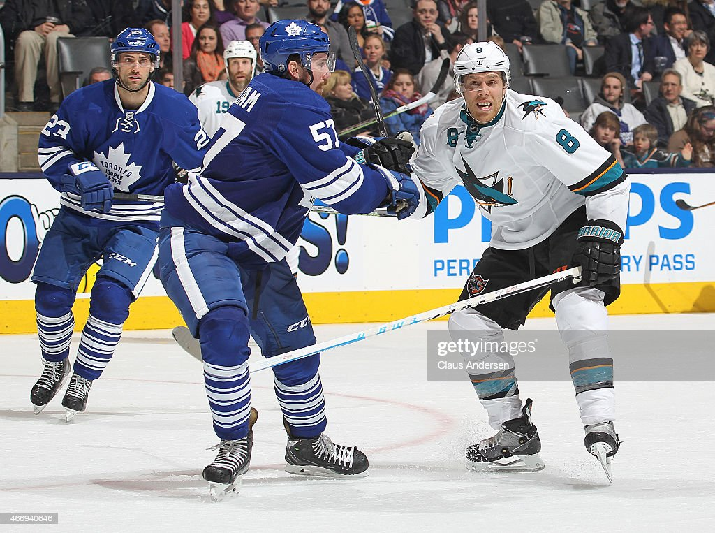 Joe Pavelski #8 of the San Jose Sharks is held up by Andrew MacWilliam #57 of the Toronto Maple Leafs during an NHL game at the Air Canada Centre on March 19, 2015 in Toronto, Ontario, Canada. The Sharks defeated the Leafs 4-1.
